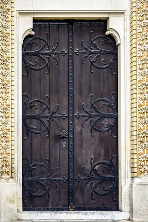 Antique wooden door decorated with wrought iron decorative elements. Beautiful design. Entrance to the historic building. Selective focus. Close-up.