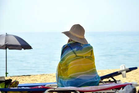 Summer vacation holidays. Beach relaxation. Elderly woman in swimsuit, pareo and panama sits on chaise-longue under an umbrella on beach and looks into distance at seascape. Back view.