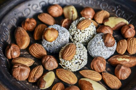 Various nuts are laid out in a brown handmade clay plate. Almonds, Hazelnuts, Brazil nuts and sweets coated with sesame seeds.  Selective focus on near candy. Blurred background. Close-up. Banco de Imagens