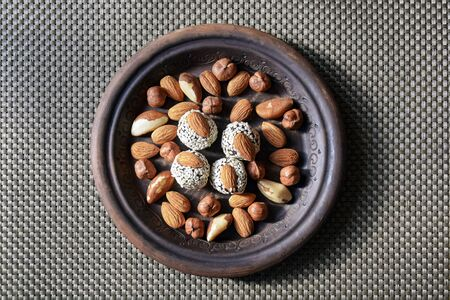 Various nuts are laid out in a brown handmade clay plate. Almonds, Hazelnuts, Brazil nuts and sweets coated with sesame seeds.  Selective focus. Close-up. Copy space.  Banco de Imagens