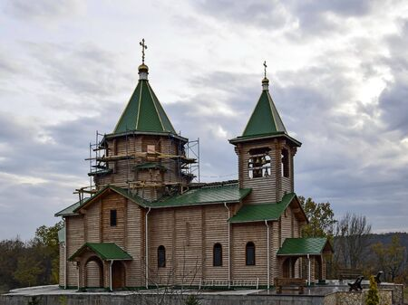 Wooden Orthodox church under construction with green roof and gilded crosses.  Finishing scaffolds mounted around the dome. View of the autumn cloudy sky. Selective focus. Close-up. Copy space.