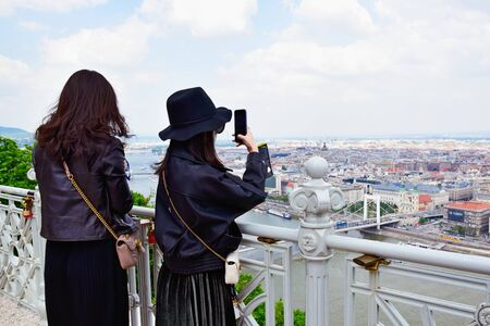 Two young asian women taking pictures of the scenic views of Budapest on smartphones from the lookout on Mount Gellert. Tourists girls use smartphone to get beautiful pictures cityscape.