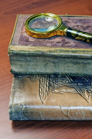 Stack of brown-bound old books with magnifying glass lie on table. Closeup. Vertical photo.