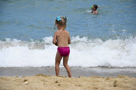 Little girl plays on seashore near splashing wave. Ñhild goes swimming in sea. Summer vacation and leisure on tropical beach. Back view.