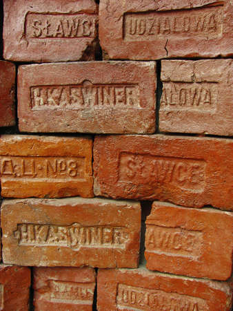 Antique red bricks with stamps of manufacturers are folded in the form of a decorative wall. Cracks and chips on old building blocks. Close-up. Selective focus. Editorial