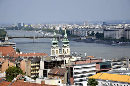 BUDAPEST, HUNGARY - MAY 2019: View on Budapest from Gellert Hill, Hungary. Ancient houses with tiled roofs and basilicas against cloudy morning sky. Panorama of the city. Editorial