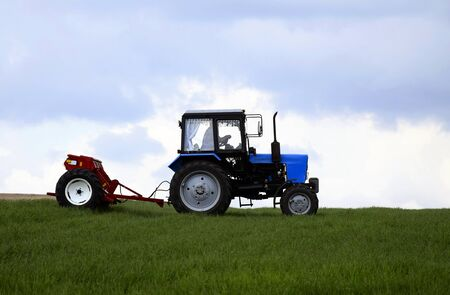Driver wheeled tractor fertilizing winter wheat with mineral fertilizers. Feeding of grain crops. Rural landscape, farmland. Selective focus. Copy space.