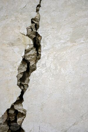 Big crack on the gray wall, abstract image of the vertical cleft. Close up. Selective focus. Copy space.