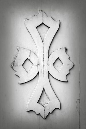 Fragment of ancient wooden door with embossed decoration in the form of cross. The old surface is covered with white paint, with traces of cracks. Close-up. Selective focus. Copy space.