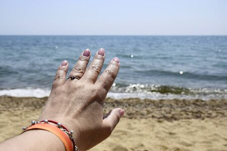Summer vacation, beach relaxation, holiday. Female hand on blurred background of blue sea on summer day. Close-up. Selective focus. Copy space.  Banco de Imagens