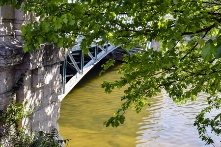 View of the river and the metal bridge through the branches with green leaves. Close-up. Selective focus. Banco de Imagens