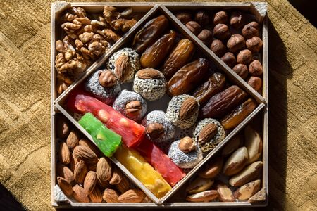 Colorful set of nuts and dried fruits in wooden package. Healthy eating concept. Almonds, Hazelnuts, Brazil nuts and sweets coated with sesame seeds. Close up. Selective focus.