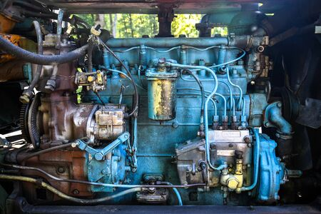 Diesel engine of an old tractor. Lots of metal tubes. Painted in blue. Close-up. Selective focus.