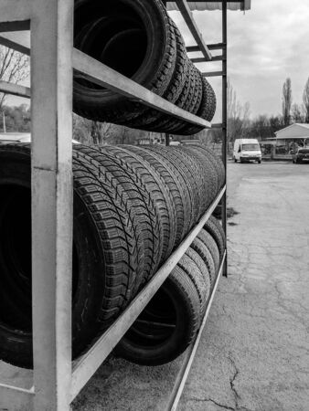 Metal rack with new tires for cars. Sale of new tires. Side view. Close-up. Selective focus. Copy space.