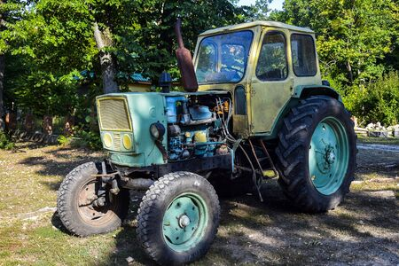 Old tractor with big wheels and rusty exhaust pipe. It stands on background of green trees. Close-up. Selective focus.