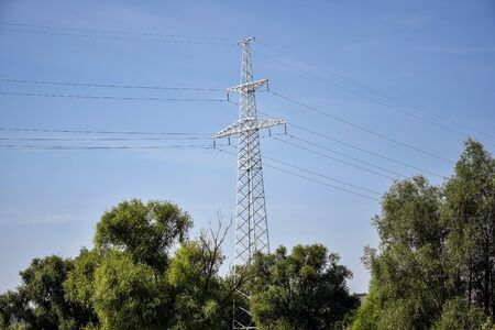 Metallic pylon of high-voltage power lines against blue sky. Located among trees with green foliage. The concept of power, transportation of electrical energy. Selective focus. Copy space. 版權商用圖片
