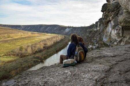 Young guy with girl sitting on the edge of cliff with legs dangling and looking at the river. Man has hairstyle with dreadlocks. Near rock monastery, carved in limestone. Close-up. Selective focus.