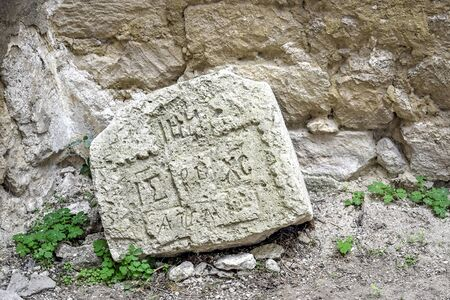 Fragment of an ancient carved gravestone against background of limestone masonry. Old burial traditions. Close-up. Selective focus. Archivio Fotografico