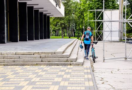 An amateur cyclist rides bicycle and goes to city park. Special sports uniform with safety helmet. Warm summer day. Healthy lifestyle concept. Selective focus. Copy space.