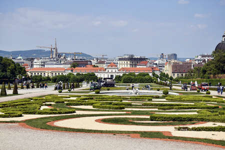Austria, Vienna - may 2019: Park of Belvedere Palace on a spring sunny day. Walking tourists. Vacations, holidays, weekends in beautiful Old Town. Tractors and cars cleaning lawns and footpaths. Editorial