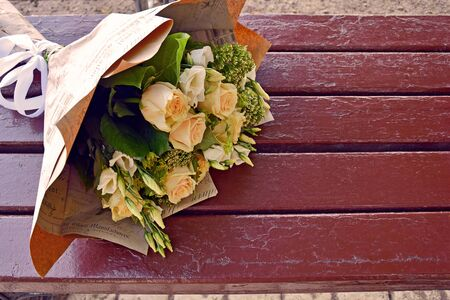 Wedding bouquet of roses in pastel colors. Bridal bouquet on the wooden surface of the old bench. Empty space for text. Close-up.