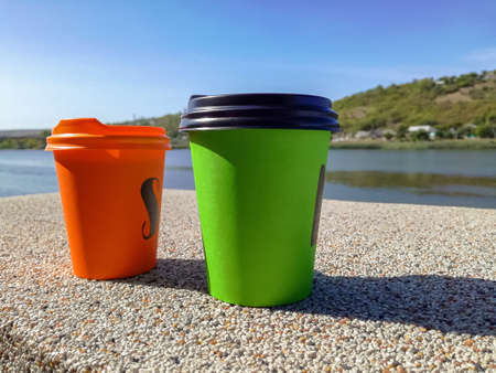 Two multi-colored disposable portable paper coffee cups of different sizes. Close-up.