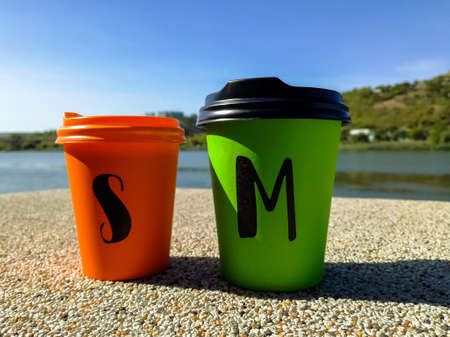 Two multi-colored disposable portable paper coffee cups of different sizes. Take-Out Coffee.Close-up.