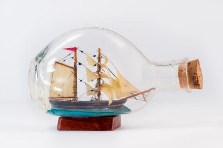 Handmade miniature ship inside a bottle isolated on white photo