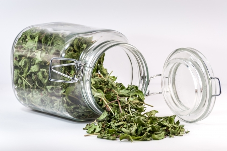 Overturned glass container with a tea leaf spilled on table.