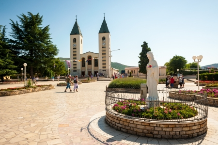 Medjugorje Sanctuary in Bosnia and Herzegovina  In the foreground is the vigin Mary statue and in the background is the parish church