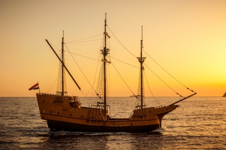 galley: Old medieval sailing ship in sunset on the open sea  Stock Photo