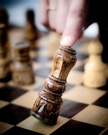 Human finger crashes down king chess piece  photo