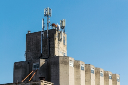 intercommunication: Industrial building with GSM antennas on roof isolated on blue sky  Stock Photo