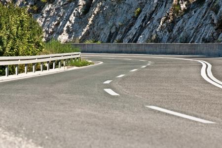 Curvy asphalt road with stone rocks in background  photo