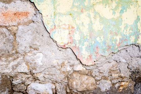 Textured wall that is crumbling tinted in yellow and light green photo