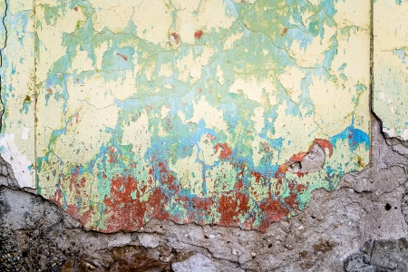 Textured wall that is crumbling tinted in yellow and light green with red stains that look like blood photo