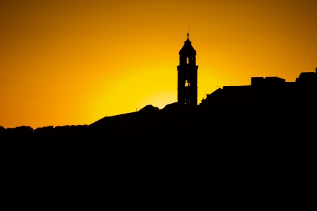 The silhouette of the city rooftops and church bell tower in Dubrovnik photo