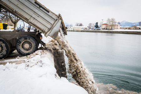 white work: Truck unloading snow into the river Stock Photo