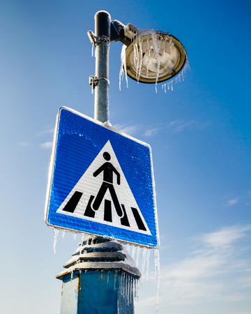Frozen road sign for pedestrians with the street lamp above photo