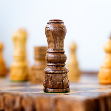 Conceptual photo of chess king standing before the set of another colour pieces photo
