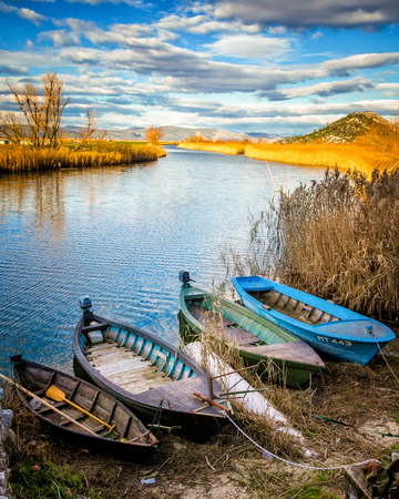 Wetland area in the south Croatian with clouds in the sky and traditional boats in front Standard-Bild