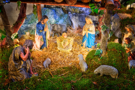 Christmas nativity scene with baby Jesus, Mary & Joseph in barn with flock of sheeps and shepherds