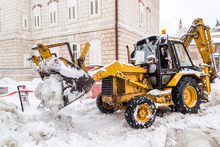 amounts: METKOVIC, CROATIA - FEBRUARY 4: Excavator cleans the streets of large amounts of snow in Metkovic, Croatia on February 4, 2012.