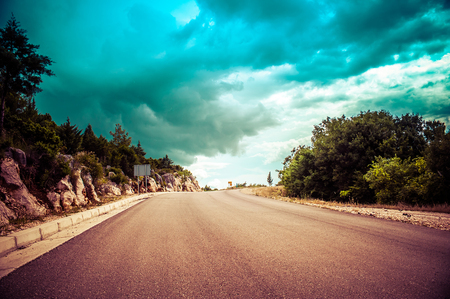 endless road: Long endless road in countryside with no traffic with dramatic clouds Stock Photo