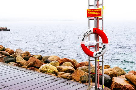 life belt: MALMO, SWEDEN - DECEMBER 31, 2014: Wooden docks and life belt by the sea on cloudy day in Malmo, Sweden.