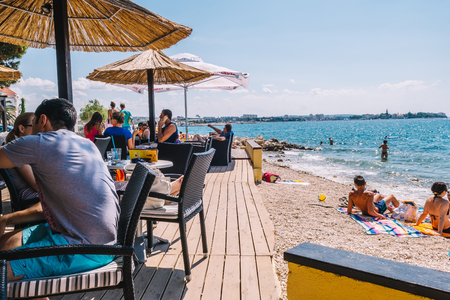 ZADAR, CROATIA - JULY 28, 2015: Tourists and various guests sitting at the bar by the sea and enjoy the sun in Zadar. Standard-Bild