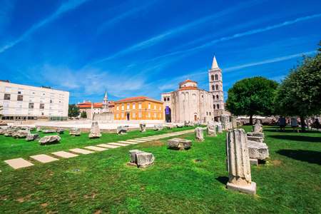 building monumental: ZADAR, CROATIA - JULY 28, 2015: Church of st. Donat, a monumental building from the 9th century with historic roman artefacts in foreground in Zadar, Croatia