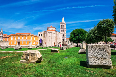 artefacts: ZADAR, CROATIA - JULY 28, 2015: Church of st. Donat, a monumental building from the 9th century with historic roman artefacts in foreground in Zadar, Croatia