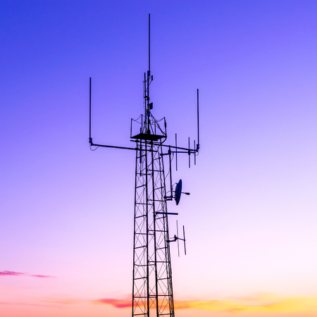 column with radio transmitter against sunset colors sky