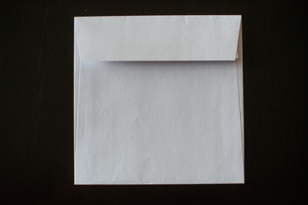 letter envelope on black background. mock-up for your design. flat lay.